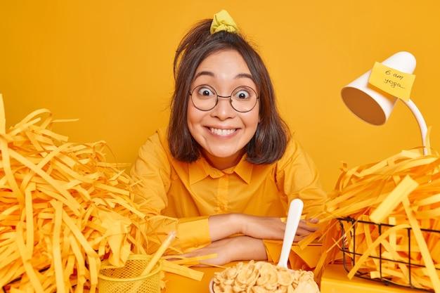 Une femme heureuse et positive qui travaille au bureau à domicile a un emploi du temps chargé dans un espace de travail entouré de papier découpé après avoir fait un projet créatif mange le petit-déjeuner prêt à commencer à travailler assis seul au bureau