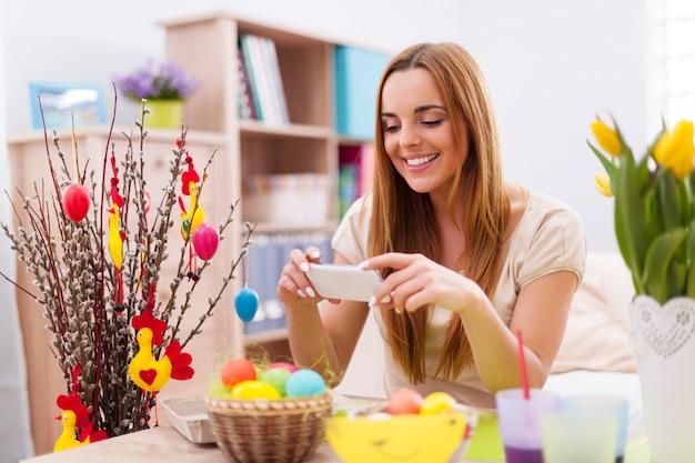 Femme heureuse prenant la photo par téléphone mobile en vacances de pâques