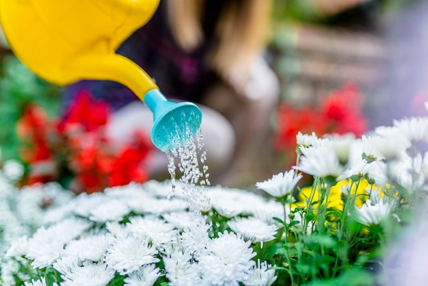 Femme heureuse en prenant soin de ses plantes (et en les arrosant) dans son jardin.