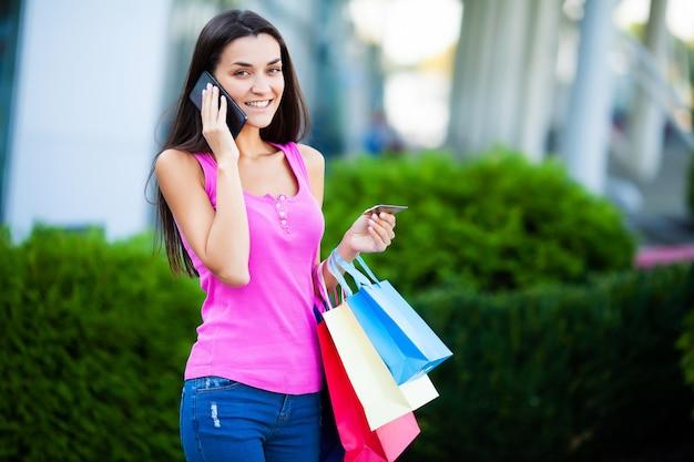 Femme heureuse, près, centre commercial, tenue, sacs cadeau, et, appeler