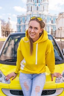 Femme heureuse près de la voiture jaune en ville en vêtements jaunes