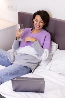 Femme heureuse en pull chaud au lit avec un verre de vin seule par elle-même au repos en regardant le film comédie sourire rire