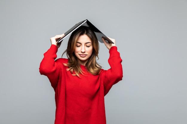 Femme heureuse en pull rouge tenant un ordinateur portable au-dessus de sa tête comme un toit sur un mur gris.
