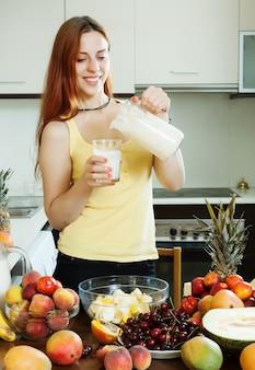 Femme heureuse qui boit du cocktail au lait avec des fruits