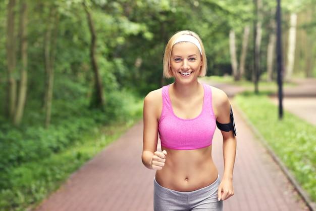 Femme heureuse qui court dans le parc