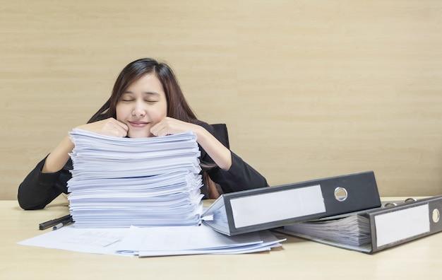 Femme heureuse qui dort après avoir terminé son travail avec du papier de travail