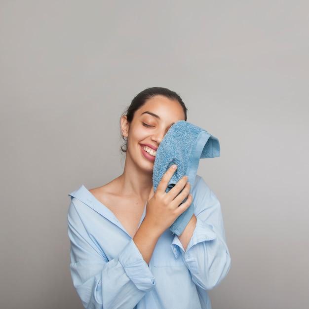 Femme heureuse qui nettoie son visage le matin
