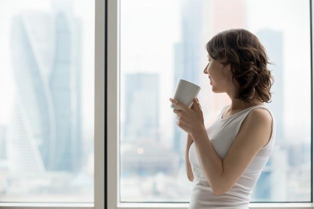 Femme heureuse qui se détend avec une boisson chaude