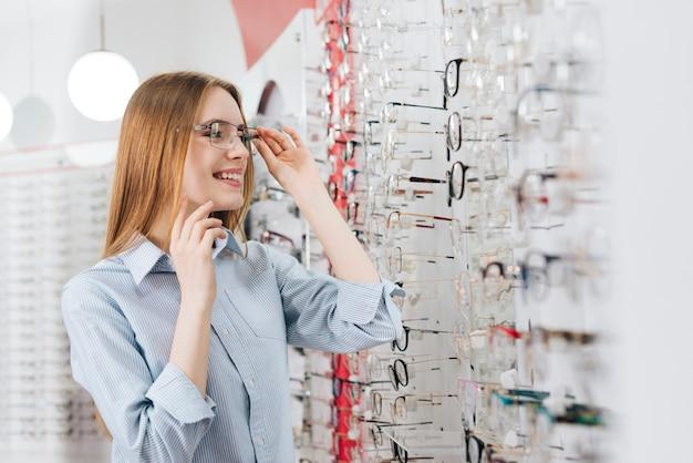 Femme heureuse à la recherche de nouvelles lunettes chez l'optométriste