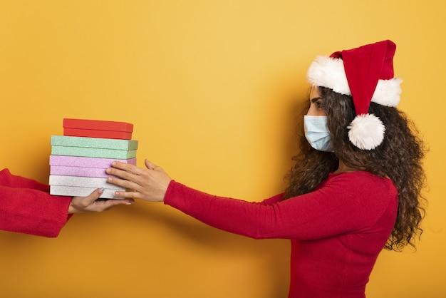 Une femme heureuse reçoit des cadeaux de noël d'un ami.