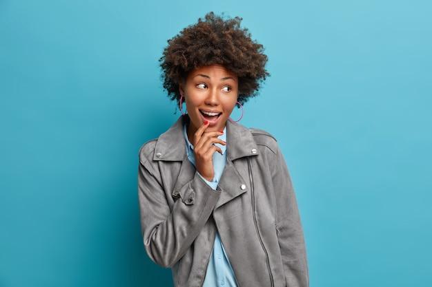Femme heureuse regarde avec une expression étonnée, garde la bouche ouverte, regarde ailleurs, porte une veste grise, surprise par des nouvelles passionnantes,