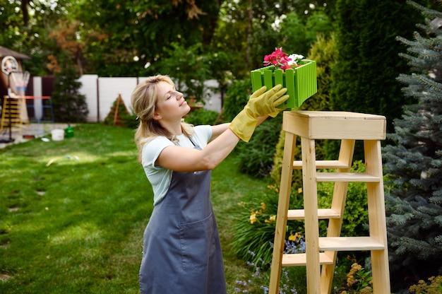 Femme heureuse regarde sur lit de fleur dans le jardin