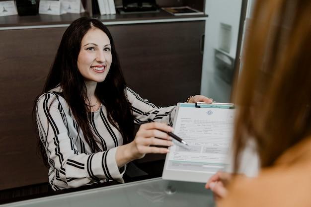 Femme heureuse remettant le contrat au client