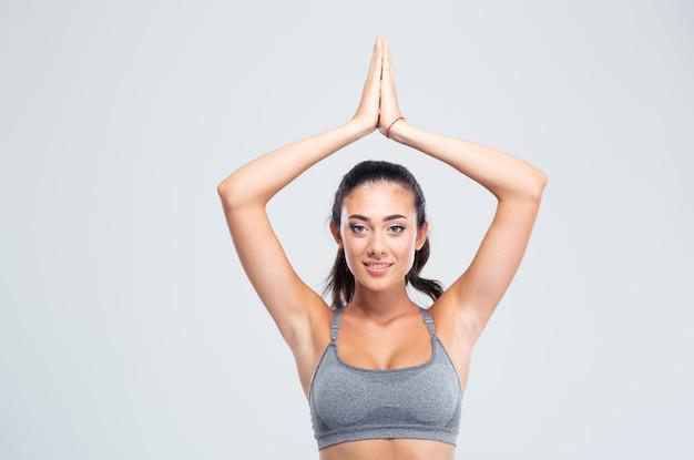Femme heureuse de remise en forme avec les mains jointes sur la tête isolé sur un mur blanc