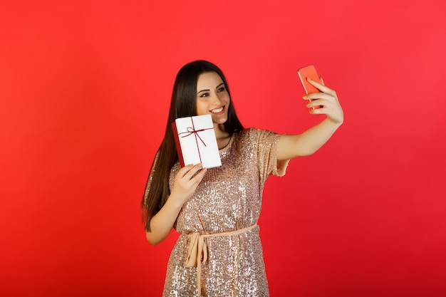 Femme heureuse en robe beige prenant selfie avec téléphone et tient une boîte-cadeau à la main