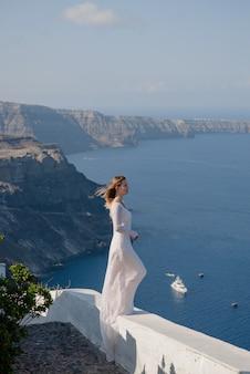 Femme heureuse en robe blanche et chapeau de paille profitant de ses vacances sur l'île de santorin. vue sur la mer égée depuis oia. destination de voyage d'été en europe. les îles greques
