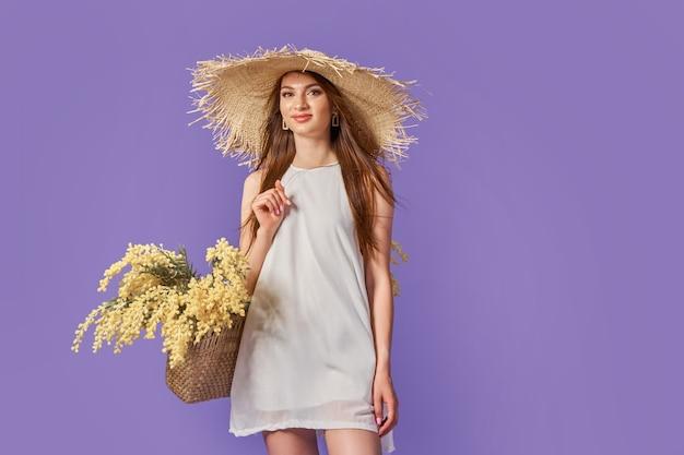Femme heureuse en robe blanche d'été chapeau de paille avec bouquet de fleurs dans un sac