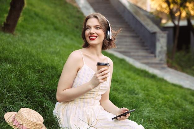 Femme heureuse en robe et casque, boire du café et écouter de la musique assis dans le parc