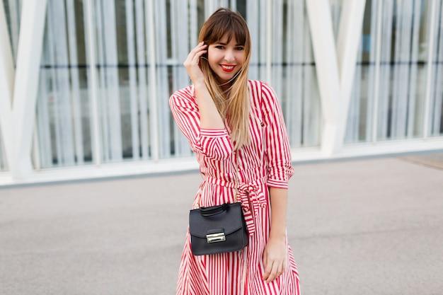 Femme heureuse en robe rouge posant dans la rue.