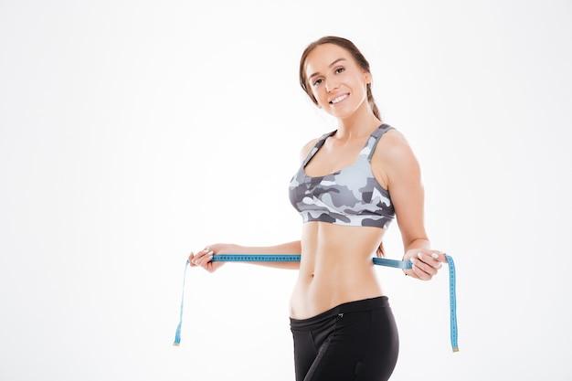 Femme heureuse avec un ruban à mesurer en studio.
