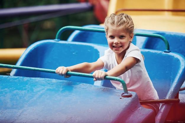 Une femme heureuse s'amuse sur des montagnes russes dans le parc pendant la journée.