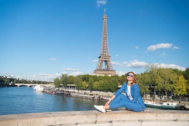 Femme heureuse s'asseoir à la rivière sur la tour eiffel à paris, france. sourire de femme dans des lunettes de soleil sur le ciel bleu. voyager en vacances d'été. rêver de paris. fille au look fashion et à la beauté sensuelle.