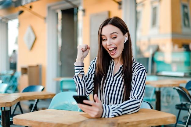 Femme heureuse de sa victoire au téléphone
