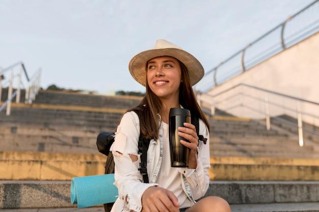 Femme heureuse avec sac à dos et chapeau tenant thermos lors d'un voyage