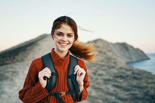 Femme heureuse avec sac à dos sur la nature dans les montagnes près de la mer et modèle de sourire joyeux au coucher du soleil