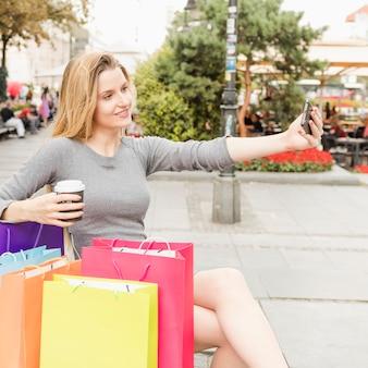 Femme heureuse avec des sacs colorés prenant selfie sur téléphone portable