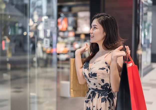 Femme heureuse avec des sacs dans un centre commercial