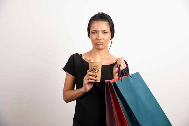 Femme heureuse avec des sacs à provisions et du café posant sur un mur blanc.