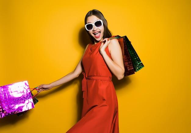 Femme heureuse avec des sacs à provisions en mains