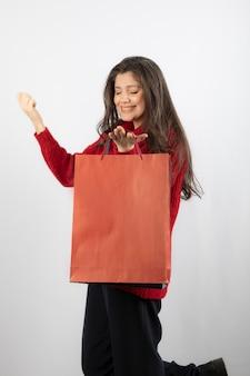 Femme heureuse avec des sacs à provisions sur mur blanc.