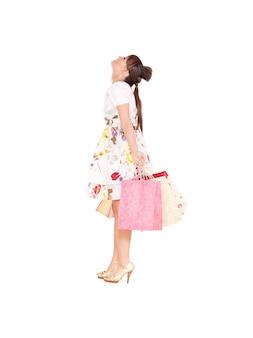Femme heureuse avec des sacs à provisions sur mur blanc