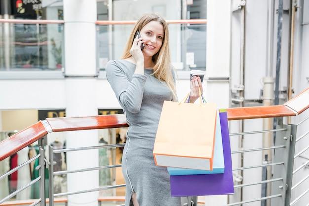 Femme heureuse avec des sacs à provisions parlant sur téléphone mobile