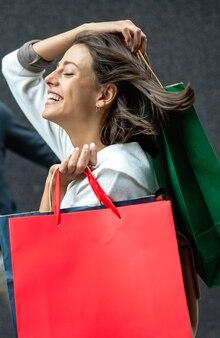 Femme heureuse avec des sacs à provisions profitant du shopping. consommation, shopping, voyage, concept de style de vie