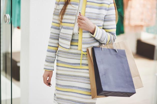 Femme heureuse avec des sacs à provisions va au magasin. l'occupation préférée de toutes les femmes, concept de style de vie