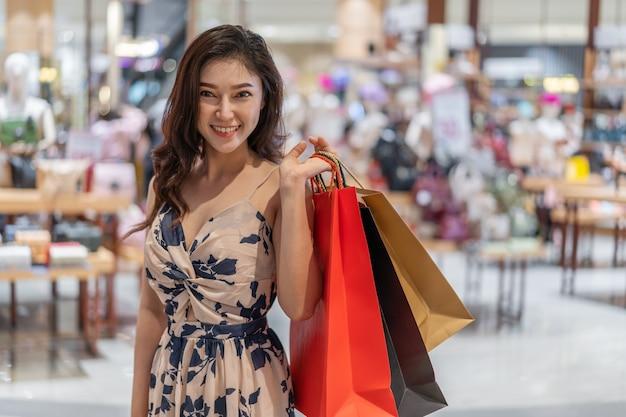 Femme heureuse avec des sacs de shopping dans un magasin de sacs à main au centre commercial