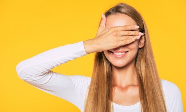 Une femme heureuse se couvre les yeux et attend la surprise