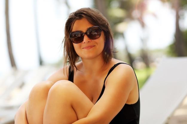 Femme heureuse se détendre sur la plage en été