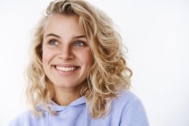 Femme heureuse se rappelant de beaux souvenirs chaleureux et tendres souriante ravie en regardant avec de beaux yeux bleus dans le coin supérieur gauche comme souvenir d'un beau moment sur un mur blanc