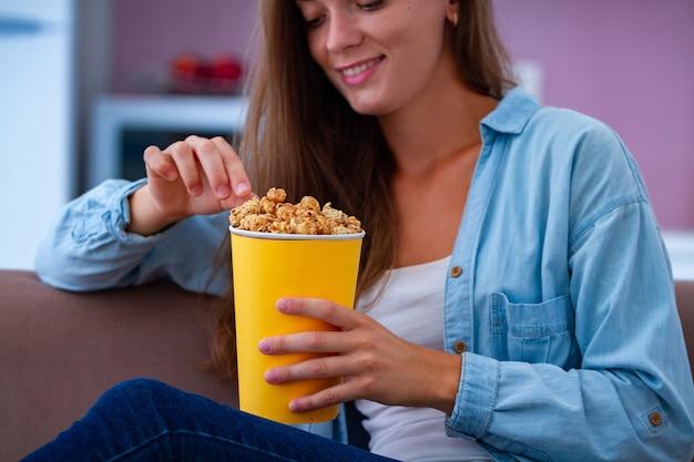 Femme heureuse se reposer et manger du pop-corn au caramel croquant pendant que vous regardez la télévision à la maison. film de pop-corn
