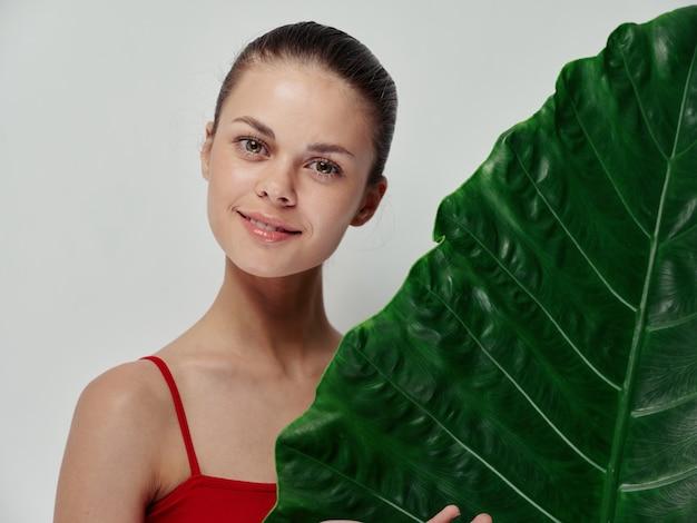 Une Femme Heureuse Se Tient Derrière Une Feuille De Palmier Sur Fond Clair Maillot De Bain Rouge Peau Propre Isolée Photo Premium
