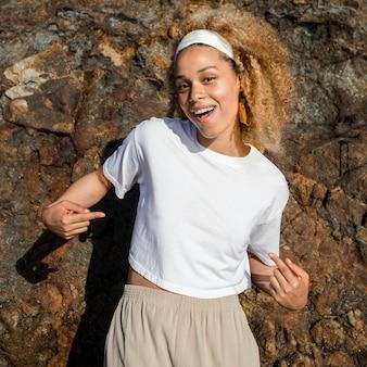 Femme heureuse en séance photo en plein air avec un haut court blanc