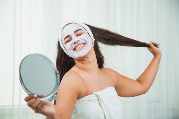 Femme heureuse en serviette et masque facial se regarde dans le miroir. traitement de beauté à domicile. concept de soins de la peau et de rajeunissement.