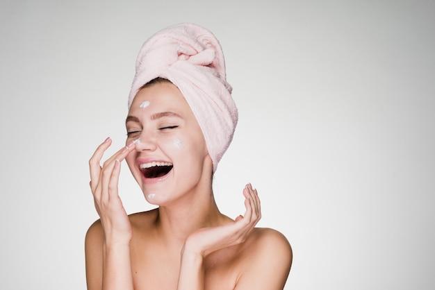 Femme heureuse avec une serviette sur la tête appliquant de la crème sur la peau du visage