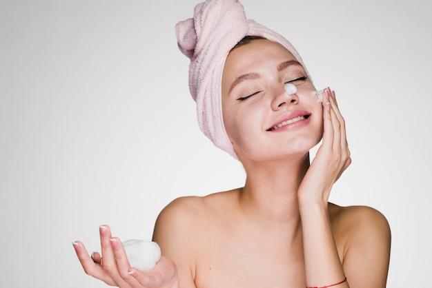 Femme heureuse avec une serviette sur la tête appliquant de la mousse sur son visage