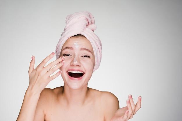 Une femme heureuse avec une serviette sur la tête a appliqué de la crème sur le visage