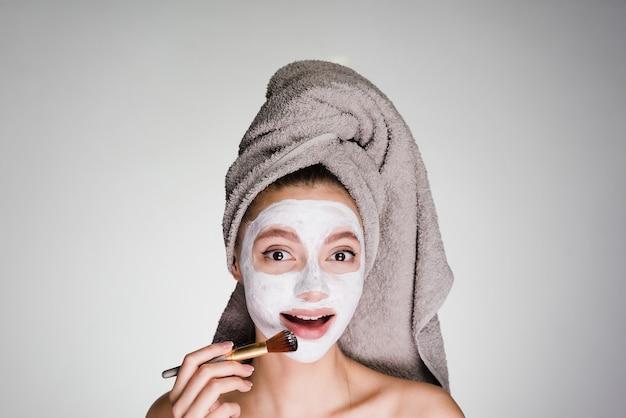 Une femme heureuse avec une serviette sur la tête applique un masque nettoyant